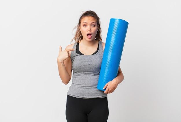 Молодая красивая женщина выглядит шокированной и удивленной с широко открытым ртом, указывая на себя и держа коврик для йоги