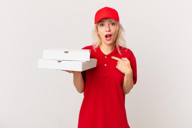 ショックを受けて驚いた若いきれいな女性は、口を大きく開いて、自分を指しています。ピザ配達のコンセプト