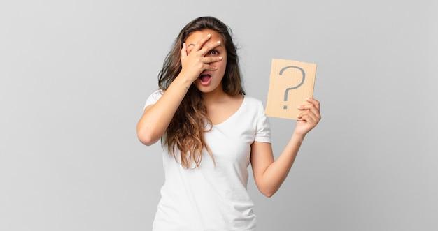 Молодая красивая женщина выглядит шокированной, напуганной или напуганной, закрывает лицо рукой и держит знак вопроса