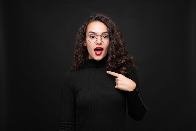 Young pretty woman looking shocked and surprised with mouth wide open, pointing to self against black wall