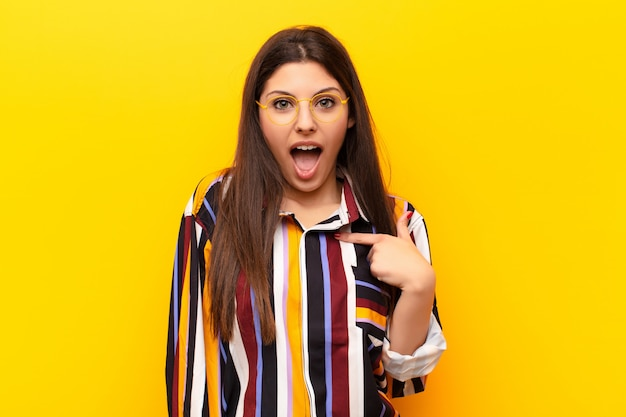 Young pretty woman looking shocked and surprised with mouth wide open, pointing to self against yellow wall