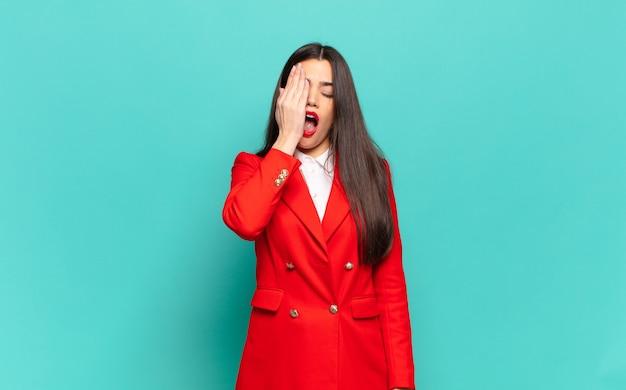 頭痛と片方の手が顔の半分を覆っている、眠くて退屈であくびをしている若いきれいな女性。ビジネスコンセプト