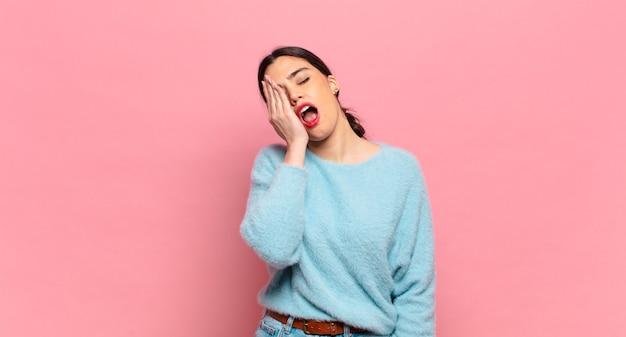 頭痛と片方の手が顔の半分を覆っている、眠くて退屈であくびをしている若いきれいな女性