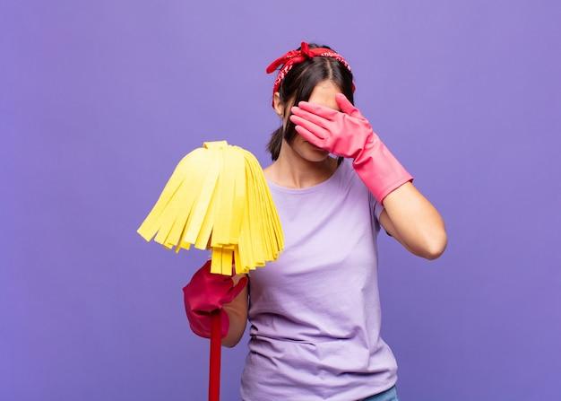 ストレス、恥ずかしがり屋、または動揺して、頭痛で、手で顔を覆っている若いきれいな女性