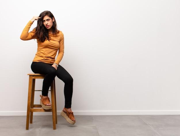 Молодая симпатичная женщина, выглядящая измотанной, уставшей и разочарованной, высыхающей пот со лба, чувствуя себя безнадежно и измученной сидя в комнате