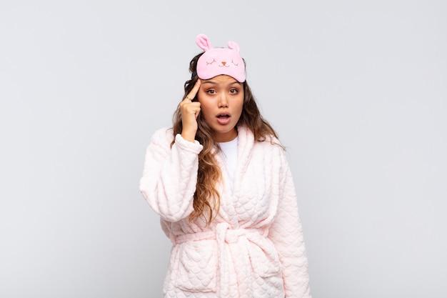 驚いて、口を開けて、ショックを受けて、パジャマを着て新しい考え、アイデア、または概念を実現している若いきれいな女性