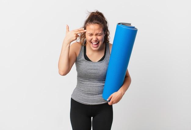 Молодая красивая женщина выглядит несчастной и подчеркнутой, жестом самоубийцы делает знак пистолета и держит коврик для йоги