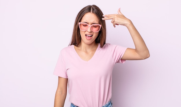 Молодая красивая женщина, выглядящая несчастной и подчеркнутой, жест самоубийства, делая знак пистолета. концепция розовых солнцезащитных очков
