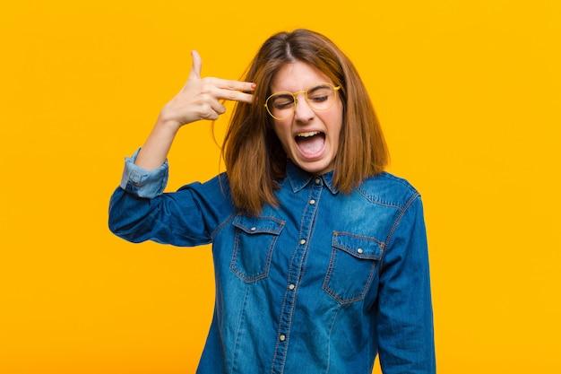 黄色の壁に頭を指している手で銃のサインを作る不幸なストレスと自殺ジェスチャーを探している若いきれいな女性