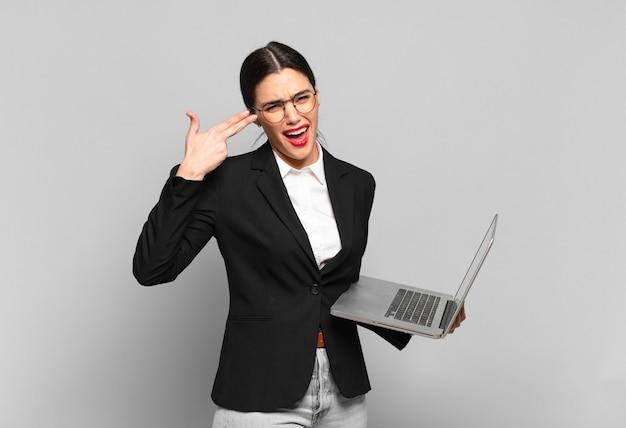 Молодая красивая женщина, выглядящая несчастной и подчеркнутой, жест самоубийства, делая знак пистолет рукой, указывая на голову. концепция ноутбука