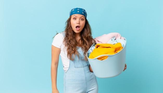 Молодая красивая женщина выглядит очень шокированной или удивленной и держит корзину для стирки белья