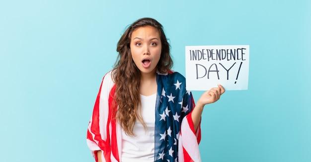 Молодая красивая женщина выглядит очень шокированной или удивленной концепции дня независимости Premium Фотографии