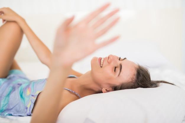 手で白いベッドとカバーカメラの下着姿で横になっている若いきれいな女性