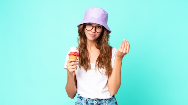Young pretty woman making capice or money gesture, telling you to pay holding an ice cream. summer concept