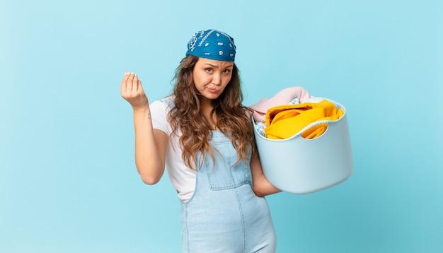 若いきれいな女性がcapiceまたはお金のジェスチャーをして、あなたに支払うように言って、洗濯かごを持っています