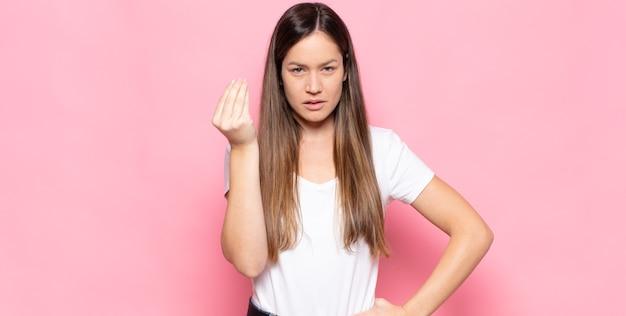 당신의 빚을 갚으라고 말하는 capice 또는 돈 제스처를 만드는 젊은 예쁜 여자!