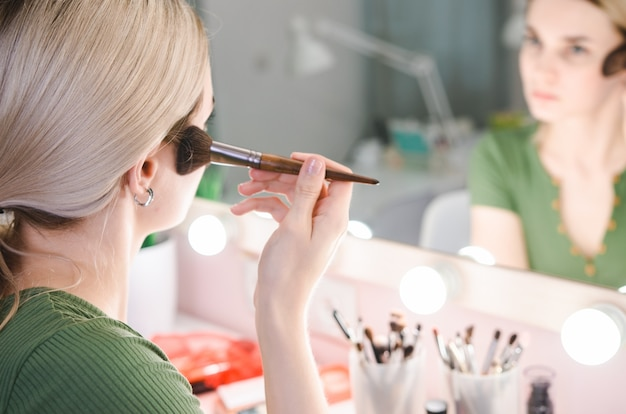Young pretty woman making make-up near mirror in studio