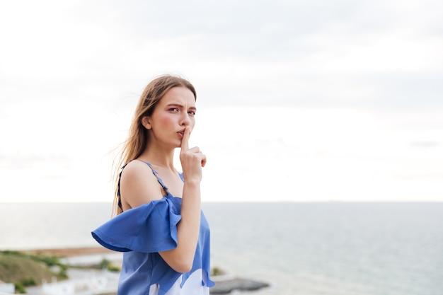 바다 위에 입술에 손가락으로 침묵 제스처를 만드는 젊은 예쁜 여자