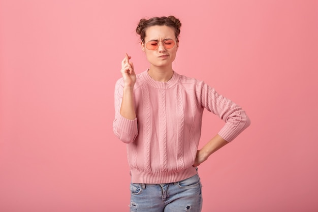 Young pretty woman making a wish crossing fingers in pink sweater and sunglasses isolated on pink studio background