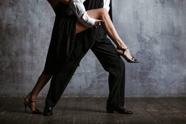 Young pretty woman and man dancing tango