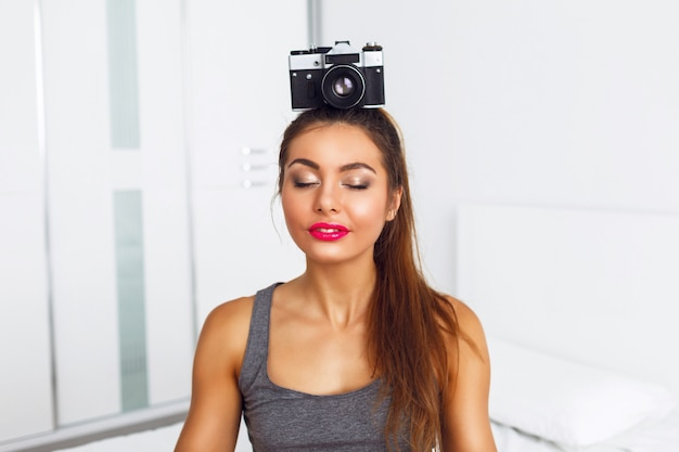 Young pretty woman meditate with vintage camera on her head