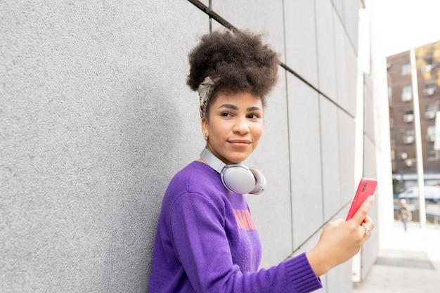 若いきれいな女性、アフロの混血、ヘッドフォンとスマートフォンで路上で幸せな笑顔、