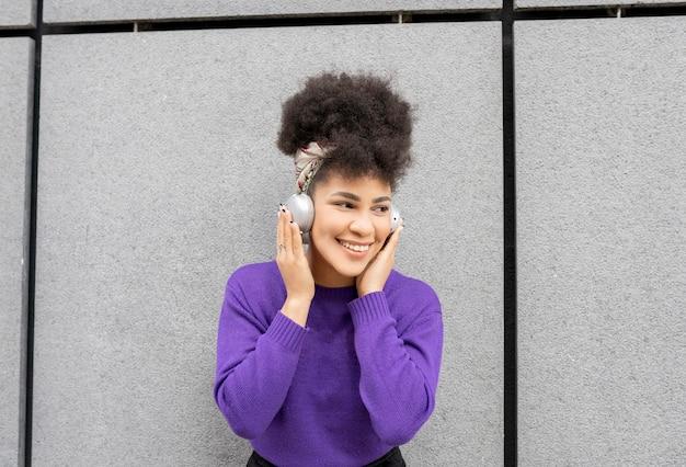 若いきれいな女性、アフロの混血、ヘッドフォンで路上で幸せな笑顔