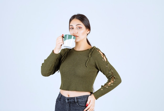 A young pretty woman model drinking from a cup and looking at the camera .