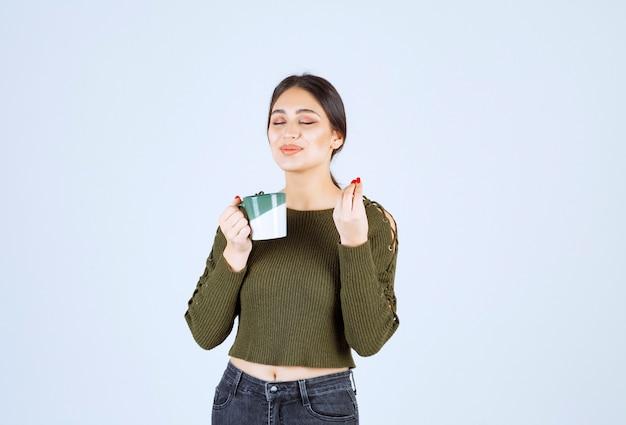 A young pretty woman model enjoying a cup of hot tea