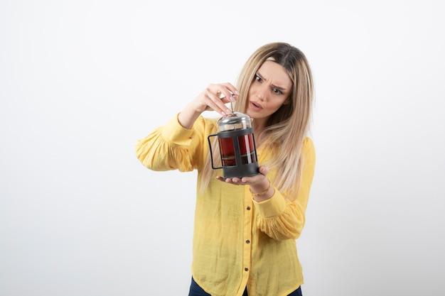 Молодая красивая женщина модель держит чайник.