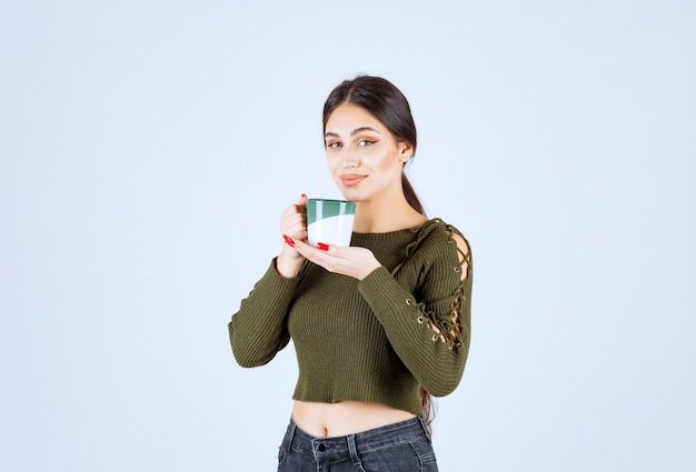 A young pretty woman model holding a cup of drink and standing .