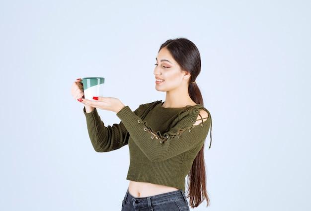 Un modello di giovane donna graziosa che tiene una tazza di bevanda e in piedi.