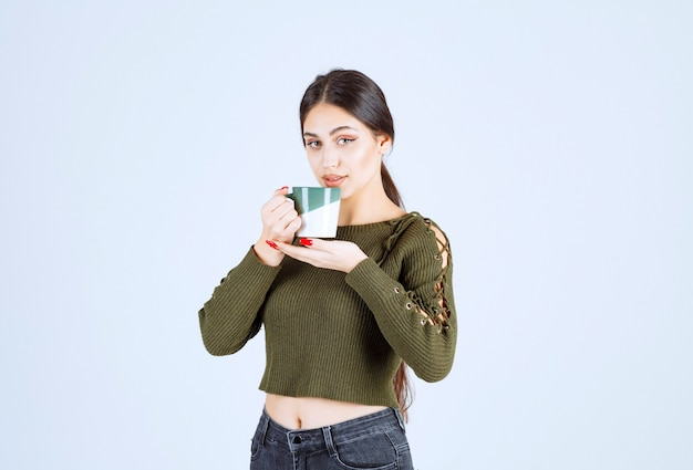 A young pretty woman model holding a cup and looking at the camera .