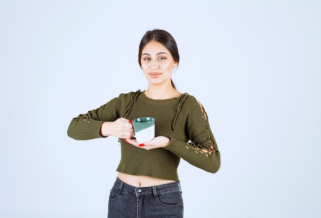 A young pretty woman model holding a cup and looking at the camera
