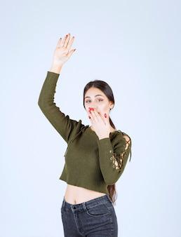 Un modello di giovane donna graziosa alzando la mano e coprendosi la bocca.