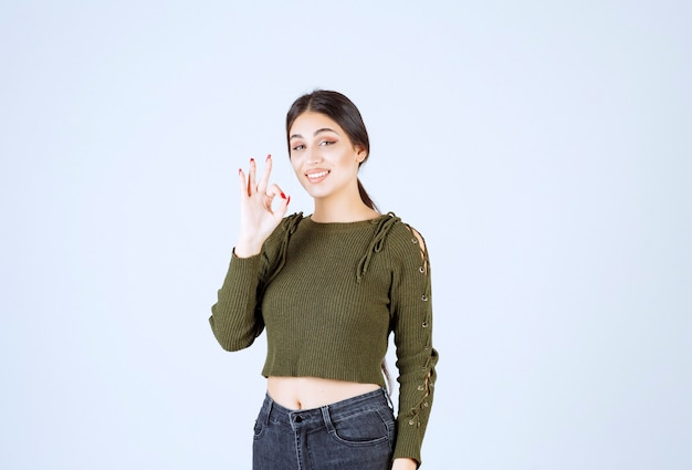 A young pretty woman model winking and showing ok gesture.