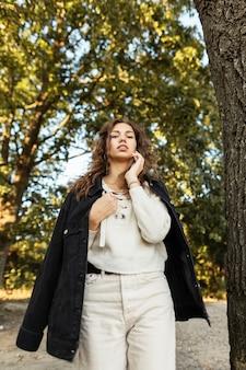 니트 구슬이 달린 세련된 데님 재킷에 곱슬머리를 한 젊고 예쁜 여성 모델이 공원을 산책하고 카메라를 쳐다본다