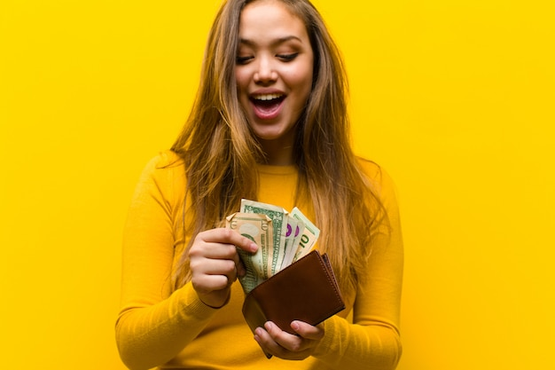 Young pretty woman money concept against orange wall