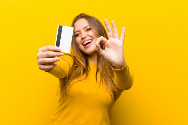 Young pretty woman money or shopping concept against yellow wall