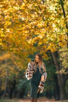 秋の公園の背景に若いきれいな女性