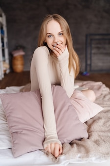 幸せで肯定的な枕でかわいい一人で自宅のベッドの上の若いきれいな女性