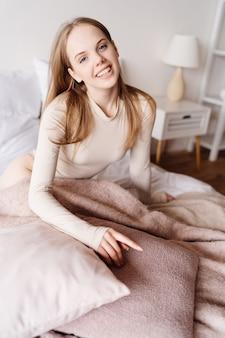 枕でかわいい一人で自宅のベッドの上の若いきれいな女性