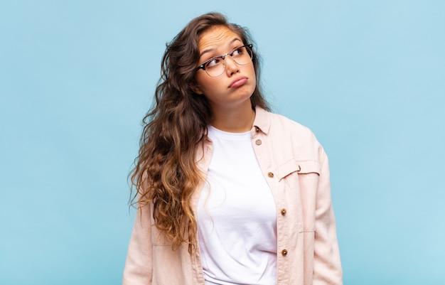 眼鏡と青い背景の上の若いきれいな女性