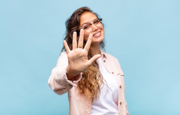 Молодая красивая женщина на синем фоне Premium Фотографии