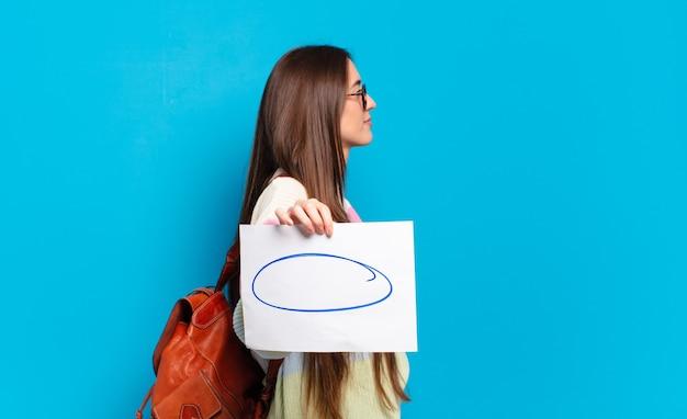 Молодая красивая женщина на виде профиля, желающая скопировать пространство впереди, думает, воображает или мечтает