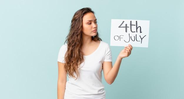 独立記念日のコンセプトを考えたり、想像したり、空想したりする縦断ビューの若いきれいな女性