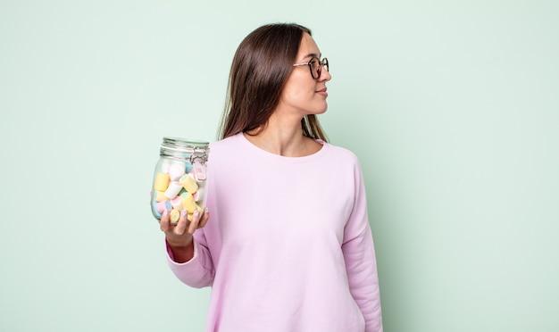 プロフィールビューの若いきれいな女性は、思考、想像、または空想にふけっています。ゼリーキャンディーのコンセプト