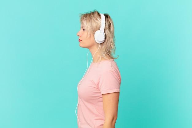 プロフィールビューの若いきれいな女性は、思考、想像、または空想にふけっています。音楽の概念を聞く
