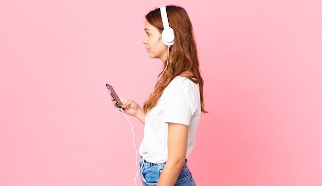 Молодая красивая женщина в профиле думает, воображает или мечтает с наушниками и смартфоном