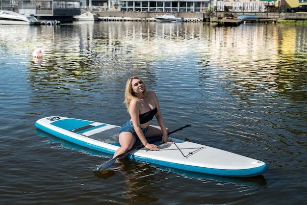 Supボードの若いきれいな女性は都市湖で夏のライフスタイルを楽しんでいます